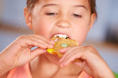 Close Up Of Young Girl Sitting At Table Eating Cookie Royalty Free Stock Image
