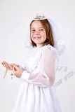 Young girl's First Communion. A close-up of a young girl smiling in her First Communion Dress and Veil, holding her rosary beads with a cross Stock Photo