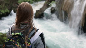 Close-up of a young girl standing with his back takes on smartphone mountain waterfall stock video