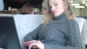 Close-up . of young girl using laptop computer for remote work on window background, technology and social network. Concept, woman hands typing on laptop stock footage