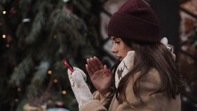 Close up of Young Girl Wearing Winter Hat and Mittens, Standing Outside and Using her Smartphone. Woman Typing, Looking stock video footage