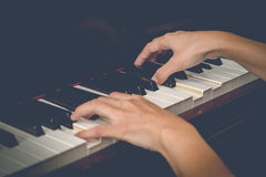 Close up of young girls hands, playing piano. vintage tone filte. R effected Stock Image