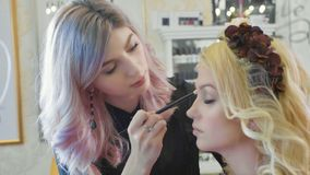 Young makeup artist applying cosmetics on model`s eyes. Royalty Free Stock Photos