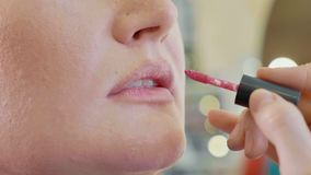 Young makeup artist applying lipstick on model`s lips. royalty free stock photos