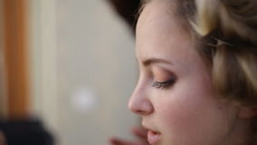 Close up of young girls`s make-up process at beauty shop. Young visagiste applying eyeshadow on model`s face. stock video