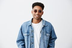 Close up of young good-looking cheerful fashionable dark-skinned man with afro hairstyle in white shirt under denim. Jacket and in sun glasses smiling with royalty free stock photography
