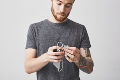 Close up of young good-looking unhappy caucasian bearded man with short dark hair and tattoo on arm in casual outfit. Holding in hands smartphone and earphones royalty free stock image