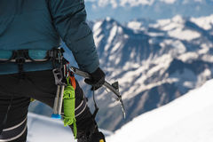 Close up A young guy climber holds in his hand an ice-ax standing on a summit high in the mountains. Extreme sport Stock Photos