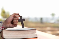 Close up young hands holding wooden cross over holy bible and praying. christian concept. N stock photo