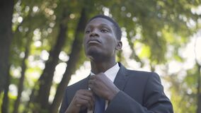 Close-up of young handsome African American man adjusting necktie in summer park and leaving. Portrait of confident