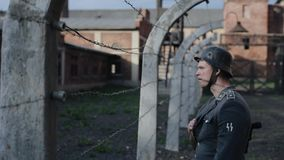 A close view of a young male actor dressed as a German soldier near a barbed wire fence guarding a death camp. A close-up of a young handsome German soldier stock footage