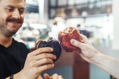 Close up of young handsome man clincing burger at cafe with friend and smiling. stock photos