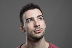 Close up of young handsome man face looking up thinking. Stock Photos