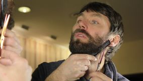 Close-up Young Handsome man trimming beard with scissors. Young man in beauty saloon working on his beard and styling stock footage