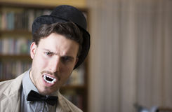 Close up Young Handsome White Vampire with Black Top Hat. Inside the Mini Library Royalty Free Stock Images