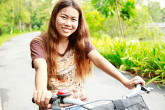 Close up young happy asia girl riding bicycle relax in a park Stock Image