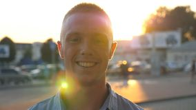 Close up of young happy businessman looking and smiling into camera at city street on sunset. Portrait of handsome stock video