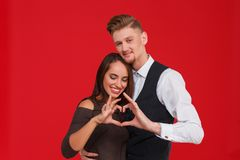 Young and beautiful couple in love make a heart on a red background. The concept of Valentine`s Day. Close-up of a young happy and fall-in-love couple is making Royalty Free Stock Photos