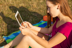 Close up. Young happy girl holding tablet pc in park. Royalty Free Stock Photo