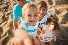 Close up of young happy loving family with small kids in the middle, having fun at beach together near the ocean, happy lifestyle. Family concept stock photo