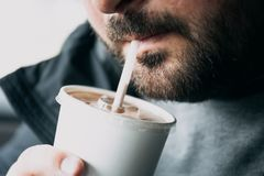 Close up of young hipster man with beard or bristle drinking chocolate cocktail through a straw Stock Photography
