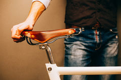 Close-up of young hipster man holding hands on his bicycle while standing indoors. Warm color. Stock Photos