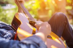 Young hipster man practiced guitar in the park,happy and enjoy playing guitar. stock image