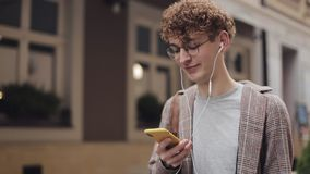 Close Up of Young Hipster Red Curly Hair Guy in Glasses with Headphones Wearing Checked Jacket. Chatting wit Friends