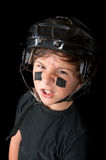Close up of young hockey player. A sweaty youth hockey player wearing his safety helmet snarls at the camera stock photo