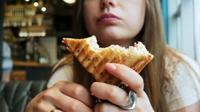 Close-up of young hungry woman eats toast in a cafe, fast food restaurant. Close-up portrait of young hungry woman with pleasure eats toast in a cafe, sharpness stock footage