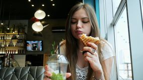 Close-up of young hungry woman eats toast and drinks a cocktail in a cafe, fast food restaurant stock footage