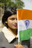 Close-up of young Indian girl holding Indian National flag covering half her face, Pune.  royalty free stock image