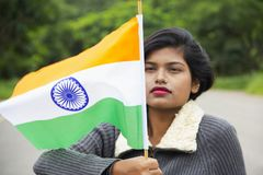 Close-up of young Indian girl holding Indian National flag and looking at it with pride, Pune.  royalty free stock photos