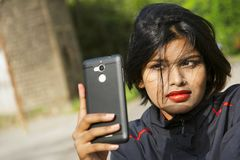 Close-up of young Indian girl with short hair wearing nose ring taking selfie, Pune stock image