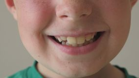 Close up of young kid smiling. Portrait of handsome boy with glad expression on face. Detail view on happy child face. Slow motion stock video footage