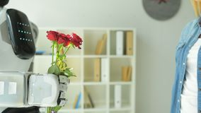 Close up young lady receiving bouquet from robot stock video footage