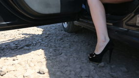 Close-up of young lady in spotted dress getting out of car and walks by road. Low angle view with focus on woman's legs stock video footage