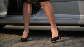 Close-Up Of Young Lady In Spotted Dress Getting Out Of Car And Walks By Road. Low Angle View With Focus On Woman`s Legs.