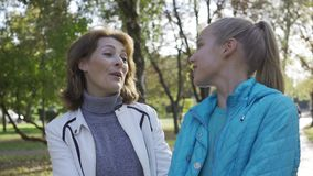 Close-up of young-looking smiling caucasian grandmother and her teenage granddaughter in casual clothes walking in the. Summer park and chatting. Good stock footage