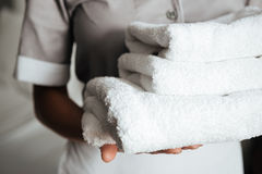 Close up of a young maid holding folded towels royalty free stock photography