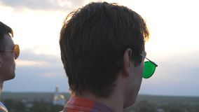 Close up of young male couple in sunglasses standing on the edge of rooftop and talking. Handsome gay boys rest on roof. Of high-rise building and enjoying stock video footage