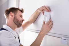 Electrician Installing Security System Door Sensor. Close-up Of Young Male Electrician Installing Security System Door Sensor On Wall royalty free stock photos