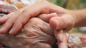 Close up of young male hand comforting an elderly arms of old woman outdoor. Grandson and grandmother spending time