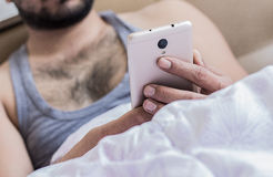 Close up of young male hands fingers working in bed on mobile phone typing sms on keyboard. Business work at home Stock Images