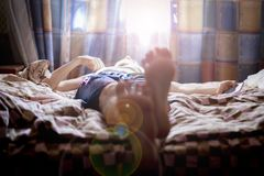 Close up young male lying on bed sleep in the mroning against the sunshine throung the window f stock photo