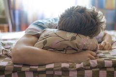 Close up young male lying on bed sleep in the mroning against the sunshine throung the window f royalty free stock images