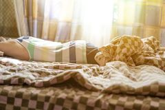Close up young male lying on bed sleep in the mroning against the sunshine throung the window f royalty free stock image
