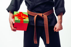 Close up Young male  with orange belt karate fighter training with gift box. Young male  with orange belt karate fighter training with gift box. Isolated on Royalty Free Stock Photo