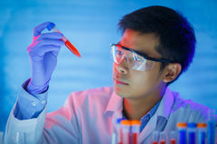 Close up of young male scientist holding test tube with blood sample making research Stock Images