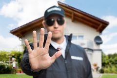 Male Security Guard Making Stop Gesture. Close-up Of A Young Male Security Guard Making Stop Gesture In Front Of A House Royalty Free Stock Photography